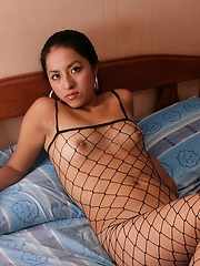 Latin chicka Jessica lies on bed in fishnet body