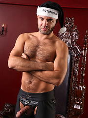 Dirty santa with hairy chest posing in leather dress