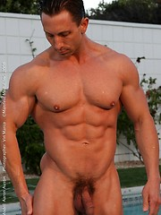 Real muscled guy posing near the pool