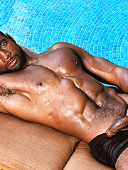 Massive black dude relaxing at the pool bench
