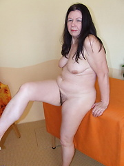 Older dark-haired granny woman get naked and showing her hairy pussy
