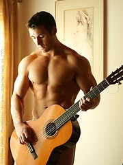 Muscular straight guy posing with guitar